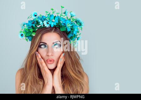 Wow. Closeup portrait jeune femme belle jeune fille avec la couronne de fleurs de serre-tête fleurs bleu à la holding excité la bouche ouverte, les mains sur les joues d'isolement Banque D'Images