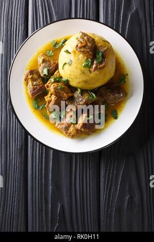 Puerto Rican Mofongo faite du plantain, de l'ail et servi avec de la viande et de chicharron broth close-up sur une plaque sur la table. Haut Vertical vue de ab Banque D'Images