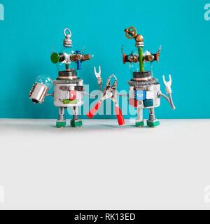Service de réparation d'entretien concept. Deux robots électricien comiques sont prêts pour l'entretien. Jouet robot handymans la lampe pince rouge, gris bleu Banque D'Images