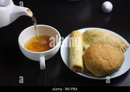 Thé et pâtisseries - Overhead shot avec une plaque blanche remplie d'un assortiment de pâtisseries et une théière verser dans une tasse de thé Banque D'Images