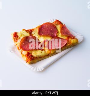 Tranche de salami pizza sur une plaque de papier isolé sur fond blanc avec copie espace Banque D'Images
