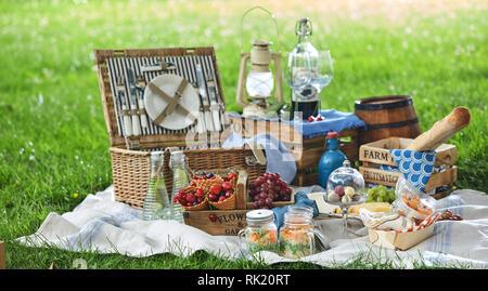 Style vintage avec déjeuner pique-nique dans un parc étendu sur un tapis sur l'herbe avec du fromage, des fruits, des bonbons, des marinades Pain et vin rouge Banque D'Images