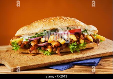Baguette croustillante appétissants remplis de boeuf barbecue et une variété de légumes y compris les frites, de la salade, de la mayonnaise et de la cuisine grecque conceptuel Banque D'Images