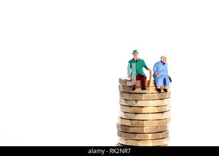 Diorama conceptuel image d'un couple de retraités figure miniture assis sur une pile de pièces livre Banque D'Images