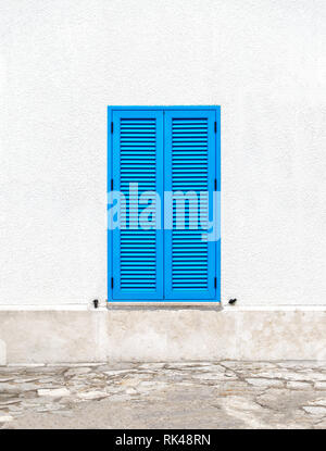 Une fenêtre avec des volets bleus sur un mur blanc dans le style grec de la ville de Santorini sur une journée ensoleillée. Banque D'Images