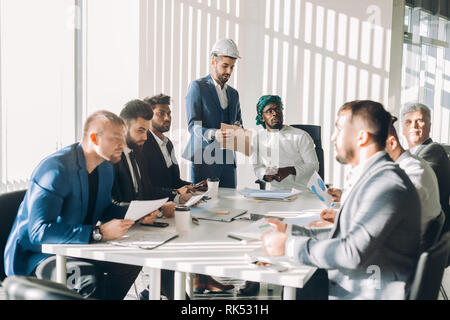 Investisseur arabe en blanc et gutra candura nationale sur la stratégie financière de l'entreprise tête de discuter avec son multirucial sexe masculin au cours d'une réunion
