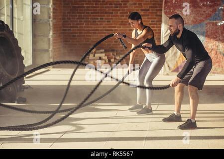 Croix tendue Active mettre en place d'un entraînement young caucasian couple en excellente forme physique, l'exercice avec des cordes en sport avec des fenêtres panoramiques et sun ra Banque D'Images