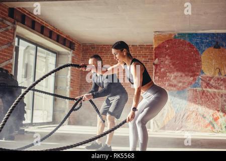 Caucasian monter beau couple dans les vêtements de sport s'est concentré sur l'exercice avec la corde de bataille nécessitant une augmentation de l'effort et la force, à l'article Banque D'Images