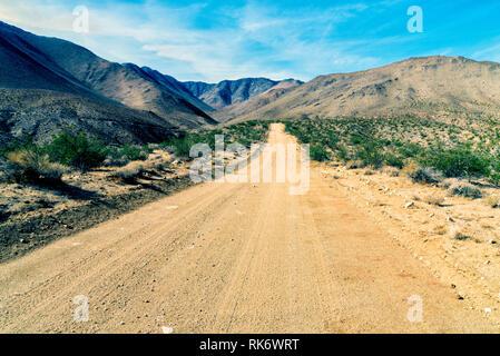 Le désert aride à la route de terre qui mène dans des montagnes du désert au-delà sous ciel bleu. Banque D'Images