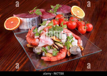 Plats en verre avec le poisson bonito mollusques et coquillages matières sur la planche de bois