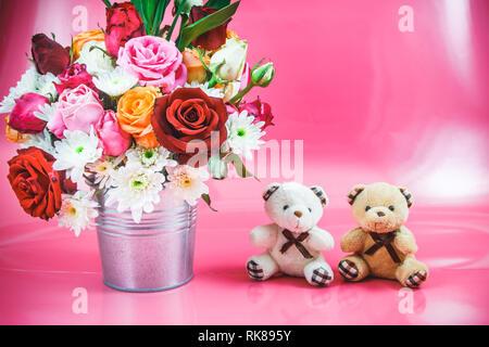 Vase de fleurs roses en godet en aluminium et quel beau couple sur fond rose. Concept de la Saint Valentin. Banque D'Images