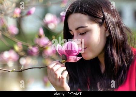 Belle fille sentant les fleurs. Magnolia en fleurs dans le parc jardin. Banque D'Images