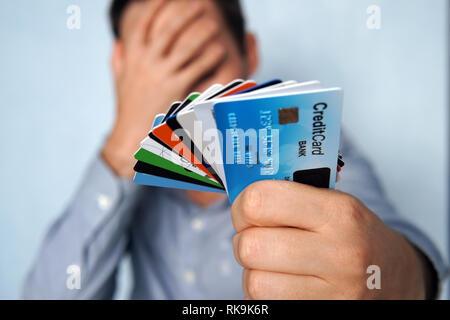L'homme confus de nombreuses cartes de crédit incertain lequel choisir sur fond bleu. jeune homme est maintenant un arrêt des cartes de crédit et de débit dans un Banque D'Images