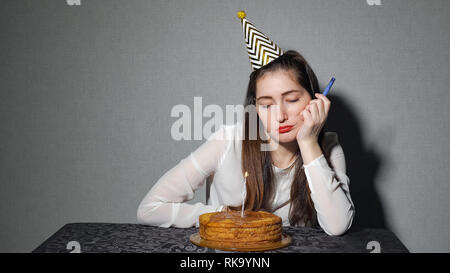 Sad lonely woman in party hat relaxing seul Banque D'Images