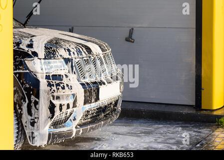 Voiture noire avec du savon blanc sur le corps en voiture de lavage. Banque D'Images