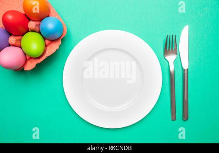 Table de Pâques, place. Les oeufs de Pâques, des couleurs pastel peint, plaque blanche vide, fond vert, copy space, vue du dessus Banque D'Images