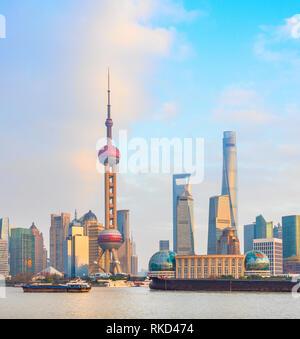 Vue de Shanghai avec les chalands par metropolis au coucher du soleil au bord de l'eau, Chine Banque D'Images