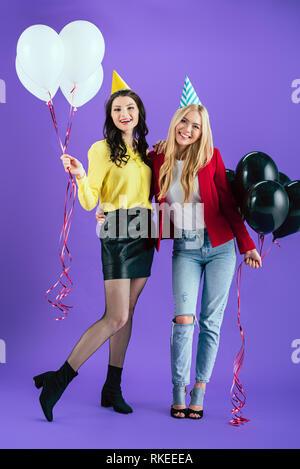 Portrait of smiling girls avec des ballons embrassant sur fond violet Banque D'Images
