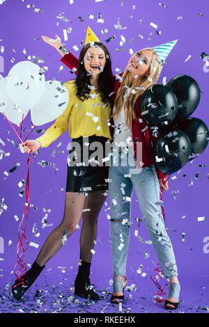 Happy in party hats posant avec des ballons sous l'éclat des confettis sur fond violet Banque D'Images