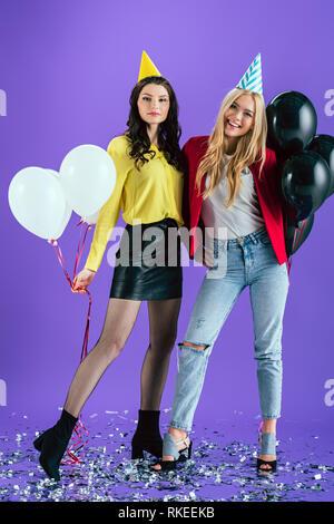 Studio shot of blissful in party hats holding montgolfières sur fond violet Banque D'Images
