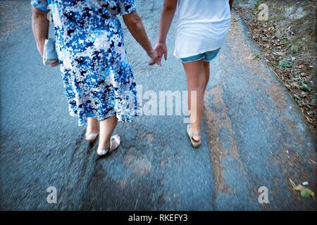 Deux femmes marchant méconnaissables se tenant la main. Santo-Pietro-di-Tenda, Corse, France. Banque D'Images