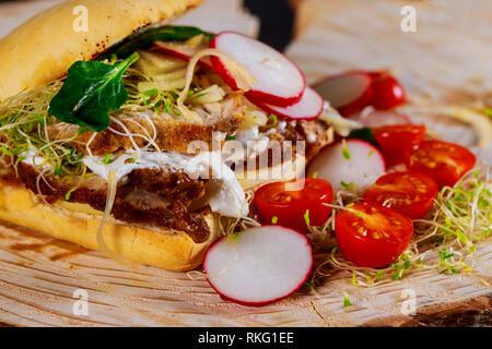 Sandwich avec viande, légumes et salade de tomates cerises, radis, oignons, fromage, sauce Banque D'Images