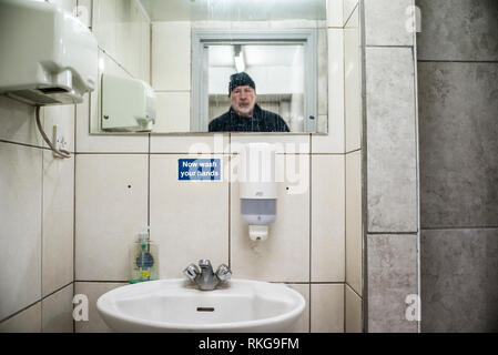 Homme barbu en miroir, se laver les mains maintenant signer, toilettes publiques, sèche-mains, distributeur de savon liquide, Banque D'Images