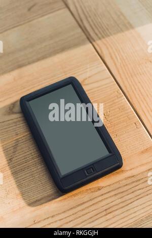 Ebook avec écran blanc allongé sur table en bois Banque D'Images