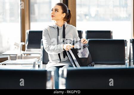 Belle jeune fille à la recherche de quelque chose et en fouillant dans le sac à dos.