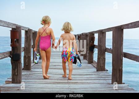 Les enfants heureux avec masque, palmes et tuba pour aller plonger en mer tropicale à l'exploration de la nature sous-marine. Style de voyage, sports aquatiques, natation adven Banque D'Images