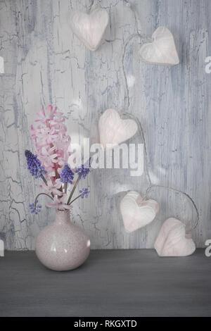 La Saint-Valentin ou fête de printemps, vase avec fleurs de la jacinthe et de la guirlande s'allume en forme de cœur sur papier de fond rustique
