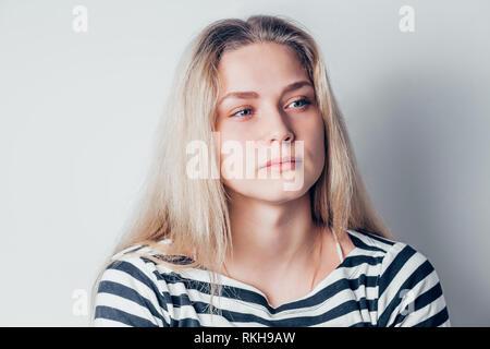 Belle jeune femme triste et grave concerné à côté et réfléchie des expressions du visage, se sentir déprimé sur fond blanc. Emotio négatif Banque D'Images