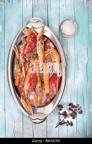 Assiette ovale avec des matières les homards et rascasses sur fond de bois, avec le gros sel et le thym fleurs, vue de dessus. Banque D'Images