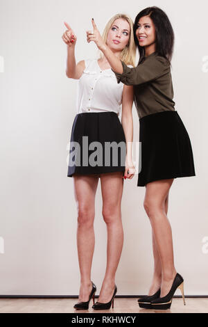 La mode et la publicité concept. Deux femmes de race blanche et de l'Afrique en pleine longueur en soulignant l'espace de copie, studio shot Banque D'Images