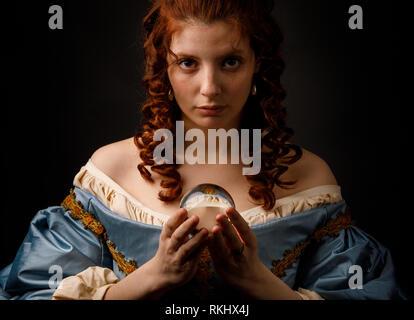 Jolie femme en tenue élégante robe médiévale petite bille de verre et à la recherche à l'appareil alors que l'article sur fond noir Banque D'Images