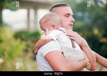 Jeune père tenant un petit enfant en pleurs en fils sunny summer la nature. Banque D'Images