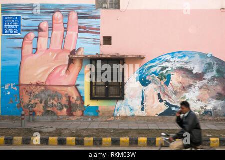 Man rides passé une murale intitulée sous les mains de l'artiste Gaia, dans Lodhi Colony, New Delhi, Inde Banque D'Images