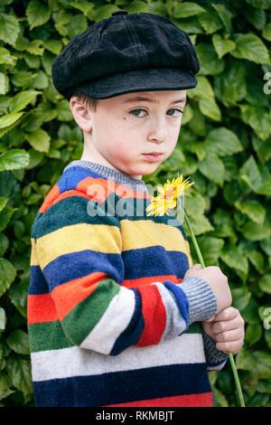 Triste, mignon petit garçon Pull rayé multicolore arc-en-ciel et noir Suède gavroche cap tenant une fleur daisy orange Banque D'Images