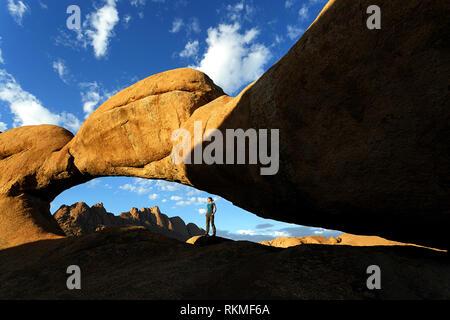 Femme debout sous l'arche de roche naturelle, près de la montagne de granit Spitzkoppe avec superbe vue sur les montagnes en arrière-plan, la Namibie, l'Afrique Banque D'Images