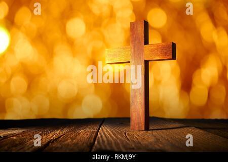La croix en bois chrétienne sur le flou des lumières et reflets fond de bois. Banque D'Images