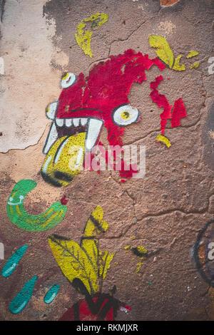 Lisbonne, Portugal - 01/03/19: red Monster Graffiti dans le centre-ville de Bairro Alto, de multiples yeux, langue jaune et des dents de vampire. Chute de peinture, taris wal Banque D'Images