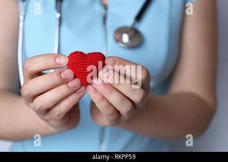 Soins de santé, cardiologie, femme médecin stéthoscope avec coeur en tricot rouge tenue en mains. Concept de cardiologue, le don de sang, de charité, de traitement Banque D'Images