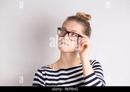 Tourné à l'intérieur de cute woman dans les verres à l'écart, ayant douteux et indécis face expression, poursuivant ses lèvres. Confus de jeunes femelles qui pose la norme iso