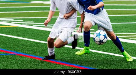 Deux garçons joueurs de football poussant et lutter les uns contre les autres pour obtenir de l'controll ballon de soccer sur un terrain de gazon vert. Banque D'Images