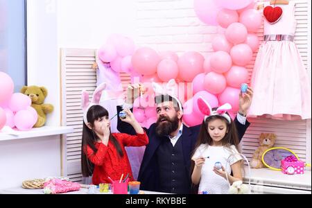 Père et filles à la main peinture d'oeufs. Banque D'Images
