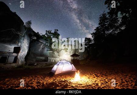 Camping au soir d'été près de mountain rocks. Brillant blanc tente et touristiques sous un feu de nuit incroyable ciel plein d'étoiles et de Voie lactée. Sur le fond beau ciel étoilé, gros rochers et arbres Banque D'Images