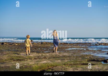 Mère et fils sont à pied le long de la plage de Bali cosmique.. Les touristes voyage Portrait - une maman avec des enfants. Des émotions positives, une vie active. Heureux Banque D'Images