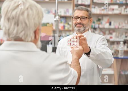 Professionnels pharmacien donnant au client blister de comprimés pour les soins de santé. Homme âgé de prendre les comprimés. L'achat de médicaments en pharmacie du pensionné. Concept de l'industrie pharmaceutique. Banque D'Images