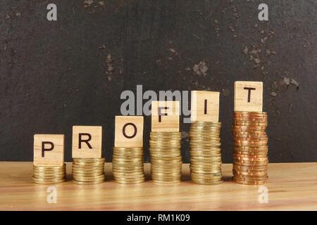 Concept d'affaires lucratif avec word sur plaque de bois sur la randonnée de pièces empilées de tendance. Banque D'Images