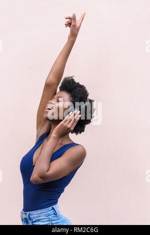 Belle happy black afro-américain young woman listening to music with headphones, sourire, danser et profiter de la vie Banque D'Images